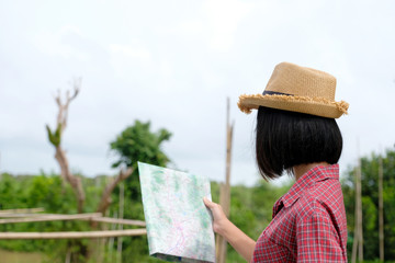 Portrait of young asian girl traveler holding map while standing in outdoors nature background, travel spring, summer holiday vacation concept, gen Z