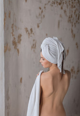 Beauty of body care, showering, clean and fresh skin concept. Naked woman in towel sitting on floor showing feet after bathing. Studio shot isolated