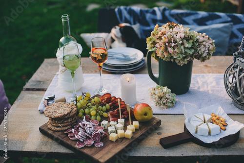 Leinwandbild Motiv wine, cheese, ham and fruits served on wooden cutting board. Summer outdoor garden party