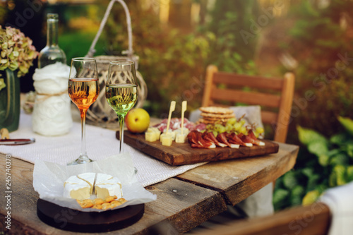 fototapeta na ścianę summer garden table decorated with flowers and candles, evening party with wine, cheese and fruits