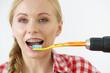Woman burshing her teeth using drill