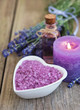 Heart-shaped bowl with sea salt and fresh lavender flowers on a old wooden table