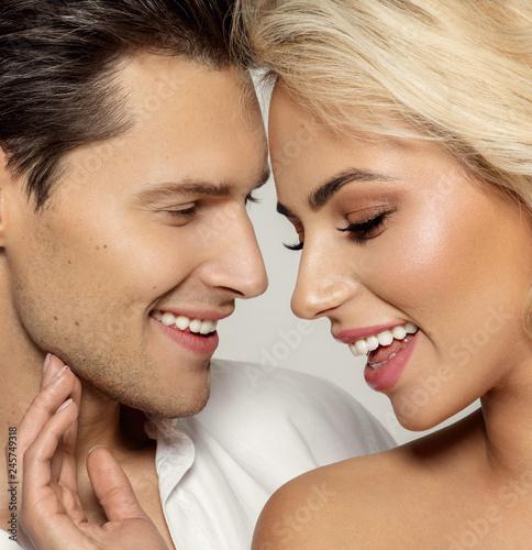 Leinwandbild Motiv Portrait of attractive loving couple isolated over gray background