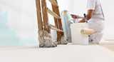 painter man at work with a roller, bucket and scale, from below view, copy space template - 245750566