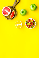 Healthy diet concept. Fruit salad near fresh fruits on yellow background top view copy space