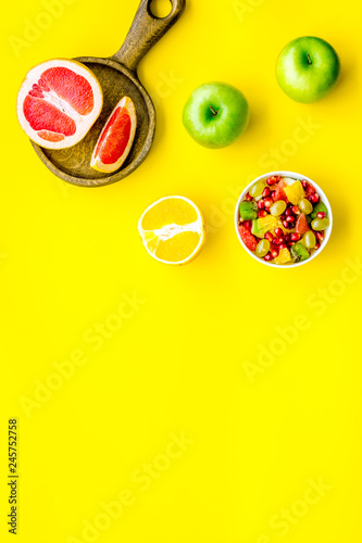 Healthy diet concept. Fruit salad near fresh fruits on yellow background top view copy space - 245752758
