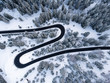 View from up of beautiful curve road in the middle of a forest full of snow in winter time.