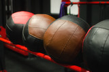 Big leather crossfit balls on the rack in the gym.