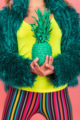 Pop art fashion girl with pineapple turquoise in the hands on a pink background. coat semi fur and tights