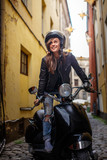 Cheerful hipster girl wearing a leather jacket and ripped jeans standing in a black classic scooter on the old narrow street