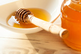 Honey dipper in a porcelain bowl with fresh honey