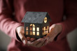 Leinwandbild Motiv Miniature house model with illuminated light in the hand