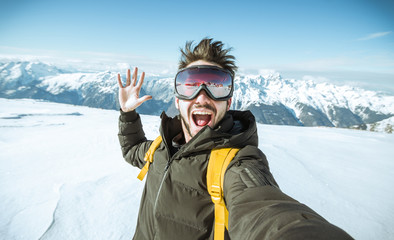Portrait of an andsome man is taking a selfie in the snow on a mountain at winter