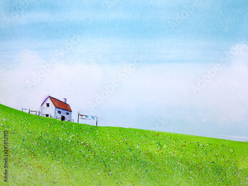 watercolor cartoon landscape countryside house in the green meadow field flower with blue sky and cloud. © atichat
