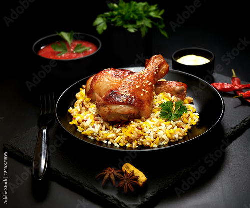 grilled chicken legs with sesame and rice on a black background. - 245871995