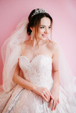 Bride in a white wedding dress posing by the window