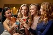 Leinwandbild Motiv celebration, bachelorette party and holidays concept - happy women or female friends clinking glasses at night club