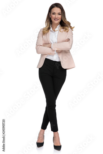 Leinwandbild Motiv confident businesswoman stands with arms folded and legs crossed