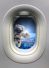 Astronaut in outer space from porthole. Elements of this image furnished by NASA.
