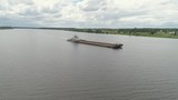 Aerial view:Barge with cargo on the river Volga. River tugboat moves cargo barge, Cargo ship on the river. - 245906545