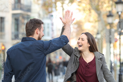Leinwandbild Motiv Excited friends giving high five in the street