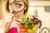 Woman investigating shopping backet with vegetables - 245909796