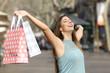 Leinwandbild Motiv Happy shopper holding shopping bags in a street