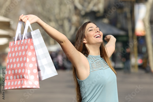Leinwandbild Motiv Happy shopper holding shopping bags in a street