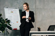 young businesswoman drinking coffee while standing by workplace in office