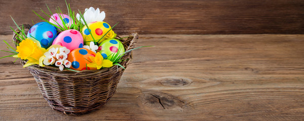 Easter eggs in basket and wooden background © PhotoSG