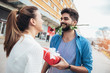 Romantic man giving flower and gift box to woman for Valentines day - 245928353