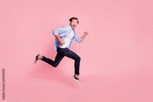Leinwandbild Motiv Full length side profile body size photo of jumping high he his him handsome run fast look oh yeah yes expression rushing wearing casual jeans checkered plaid shirt isolated on rose background