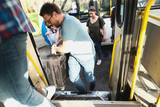 Small Group of people entering bus. Selective focus on Man with luggage.