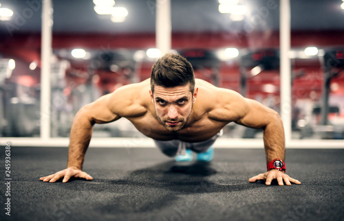 Shirtless Caucasian man doing push ups on gym floor. In background mirror.