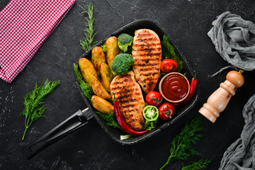 Baked chicken fillet with carrot and vegetables on a black stone background. Top view. Free copy space.