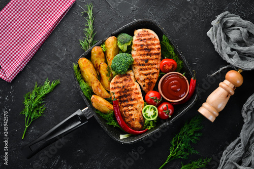 Baked chicken fillet with carrot and vegetables on a black stone background. Top view. Free copy space. - 245942578