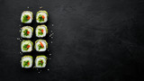 Sushi roll with avocado, cucumber and tomato. Japanese cuisine. Top view. On a black background. - 245947701