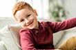 A Cute redhead boy sit on the sofa at home