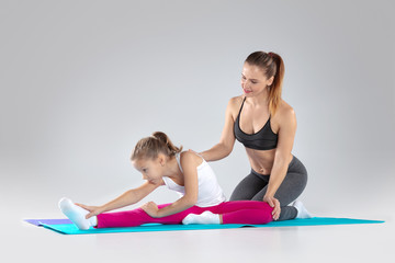Fitness woman and her daughter are doing exercises on mats © alexsokolov