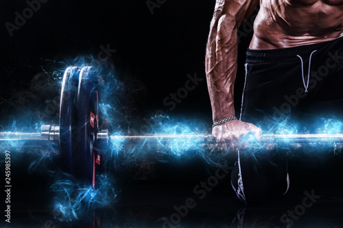 Leinwanddruck Bild Closeup photo of strong muscular bodybuilder athletic man pumping up muscles with barbell on black background. Workout energy bodybuilding concept. Copy space for sport nutrition ads.
