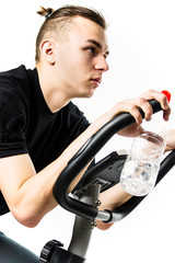 young man rides a stationary bike on a white background, sports © mikitiger
