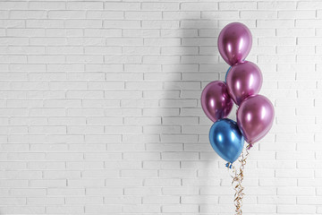 Bright colorful balloons near brick wall, space for text. Party time