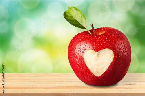 Leinwanddruck Bild Red apple with a heart shaped