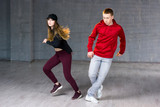 Modern style dancers performing hip-hop. Couple of casual style teenagers dancing contemporary dance on studio background.