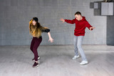 Attractive casual couple dancing hip-hop. Two modern style beautiful performers working out on studio background.