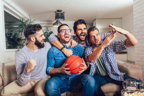 Fototapeten Basketball Happy friends or basketball fans watching basketball game on tv and celebrating victory at home.Friendship, sports and entertainment concept.
