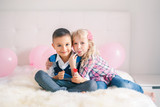 Group portrait of two happy white Caucasian cute adorable funny children eating heart shaped lollipops. Boy and girl celebrating Valentine Day. Love, friendship and fun. Best friends forever. - 246001135