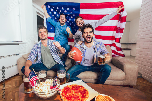 Male friends watching tv and cheering sport games on sofa at home. Group of friends watching american football match.