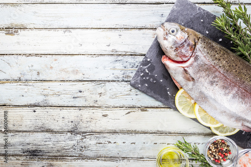 Raw trout fish on slate with rosemary and lemon over white wooden table, top view - 246004918