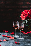 Two wine glasses of rose wine on brick background, bouquet of red roses for romantic evening for Valentines day surprise, marriage proposal passion and love celebration, copy space  - 246014107